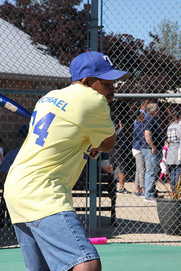 Michael Baker of the Dandy Lions eyes the ball just before he takes a powerful swing - Moody Miracle League